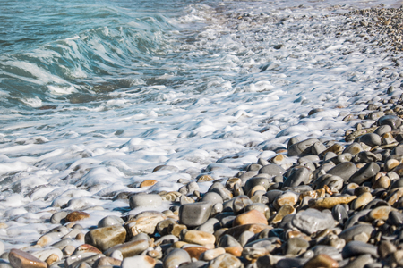 Serene waves lapping over petals on a beach. Stock Photo