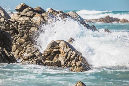 Dramatic crashing wave behind rocks on the shore. Stock Photo