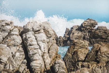 Dramatic crashing waves behind rocks on the shore. Stock Photo