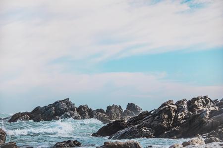 Dramatic crashing waves hitting rocks on the shore.