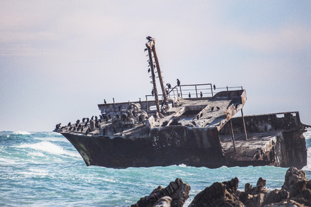 Rusted old shipwreck on a rugged rocky coastline.