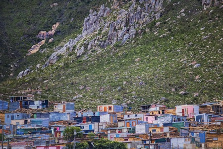 Shack homes in township below massive mountain in Kleinmond, Western Cape, South Africa.