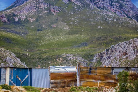 Medium shot of shack homes in township below massive mountain in Kleinmond, Western Cape, South Africa.