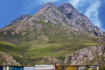 Wide shot of shack homes in township below massive mountain in Kleinmond, Western Cape, South Africa.
