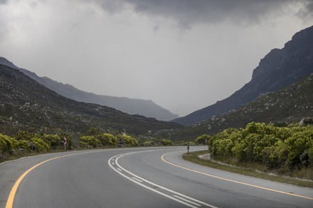 Road path through mountain range on Clarence Drive, Kleinmond, Western Cape, South Africa. Stock Photo