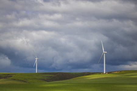Dramatic thunderstorm over wind turbines in green fields - Caledon, Western Cape, South Africa.