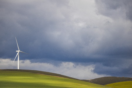 Dramatic thunderstorm over wind turbine in green fields - Caledon, Western Cape, South Africa.