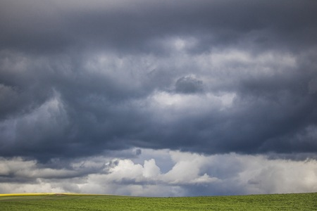 Minimalism photo of a dramatic clouds over a green field.