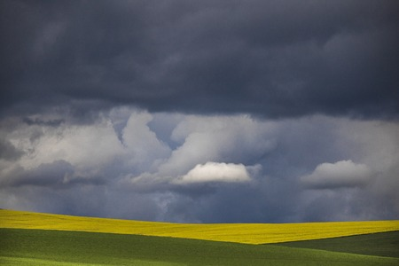 Minimalism photo of a dramatic clouds over a green and yellow fields.