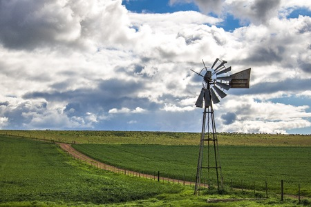 Windmill next to a dirt road in a green field in Caledon, Western Cape, South Africa. Stock Photo