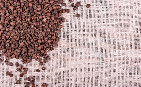 Roasted coffee beans on sack fabric background
