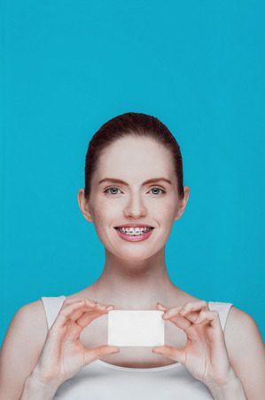 overbite: Happy beautiful girl with braces and white card in hands on cyan background