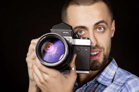 photocamera: Emotional man with photocamera in hands on black background