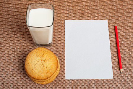enumeration: cup of milk, biscuits, piece of paper and pencil Stock Photo