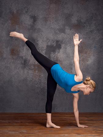 ardha: yoga woman standing on one leg, copy space for text or slogan (ardha chandrasanu)