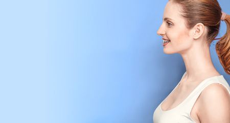 overbite: Profile of beautiful girl face with braces on blue background Stock Photo