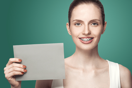 Happy beautiful girl with braces and gray card in hands on green background