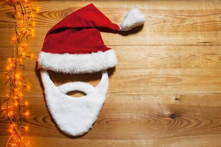a place for the text: beard and Santa hat lying on a wooden table with a garland, a place for text congratulations Stock Photo