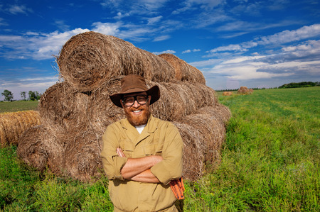 hay field: Portrait of smiling farmer with arms crossed in hay field Stock Photo