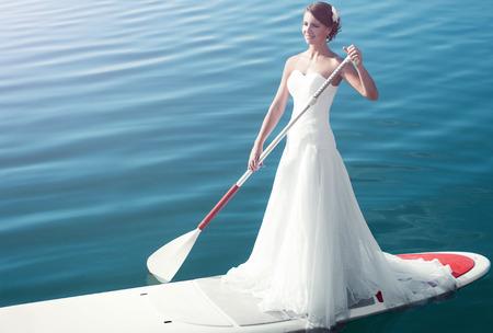 물에 패들 보드가있는 흰 드레스를 입은 소녀가 물 위에 떠 있습니다.