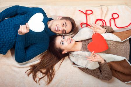 bacio: coppia che si bacia dietro cuore di carta