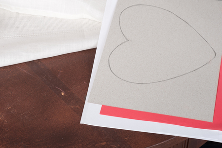 paper cutout: heart drawn in pencil on paper cut-out Stock Photo