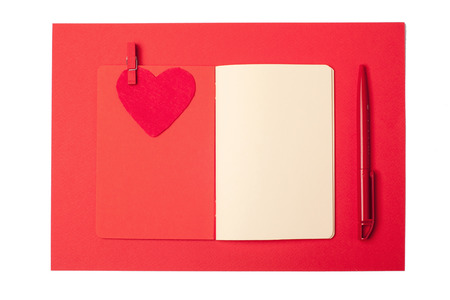red pen: Red heart, red pen and red notebook. Isolated over white background.