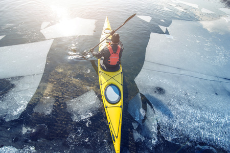 frozen river: man kayak is on a frozen river