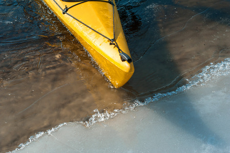 adverse: lonely yellow kayak on the river ice, boat detail