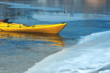 snow break: lonely yellow kayak on the river ice, boat detail
