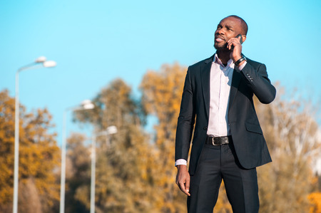 black professional: a black man in a business suit standing street and uses two phones