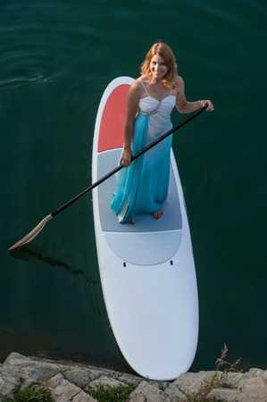 sup: SUP the girl in a white dress with a paddle board floats on water, near the shore Stock Photo