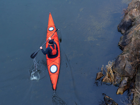 adverse: man paddles a red kayak on the river near the shore, kayaking