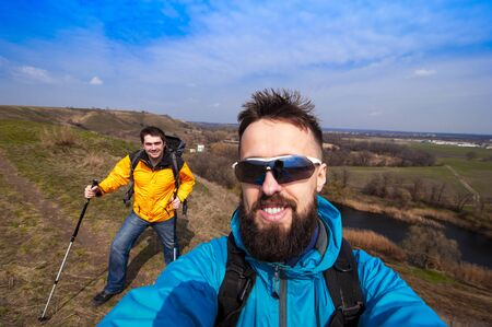 holiday maker: male with friend hiker taking photo with smartphone in forest, looking at camera, copy space for text or slogan Stock Photo