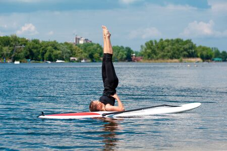 stand up paddle board yoga performed by beautiful girl on the bright city background, yoga training on the beach