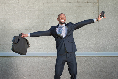 african business man: African American business man is happy standing on a gray background urban wall