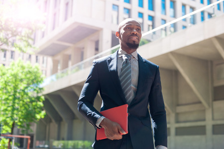 uses a computer: black man in a business suit standing street and uses phones and tablet computer