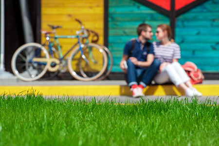 diffuse: happy young couple kissing on the background of a bike, diffuse focus