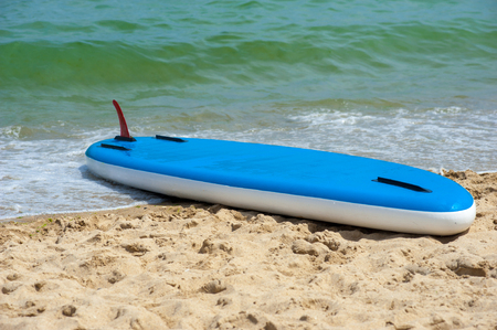 surfboard fin: rubber stand up paddle board is upside down on the beach in the sand SUP Stock Photo