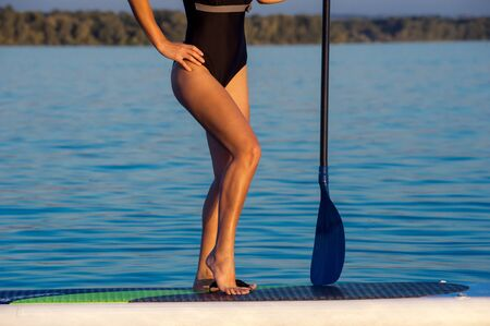 sup: SUP confident woman swimsuit standing with a paddle on the surfboard, legs Stock Photo
