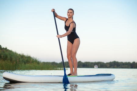 sup: SUP confident woman swimsuit standing with a paddle on the surfboard Stock Photo