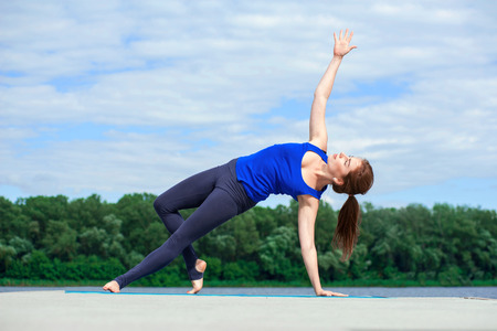 young woman practicing advanced yoga by the lake, sitting on the dock.  Concept healthy lifestyle. closed eyes