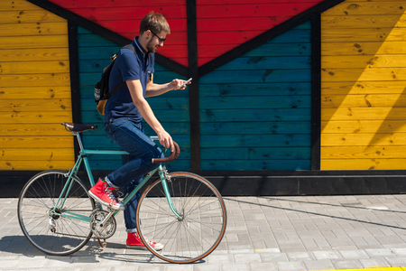young funny man with a hire bike checking her phone, space for text