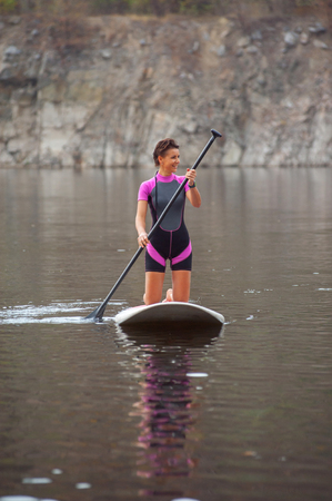 confident woman standing with a paddle on the surfboard, yoga, fitness Stock Photo