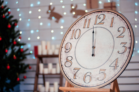 12 days of christmas: vintage clock with an arrow in the room with the Christmas tree, space for text five minutes before midnight Stock Photo