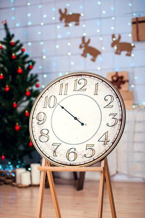 specify: vintage clock with an arrow in the room with the Christmas tree, space for text five minutes before midnight Stock Photo