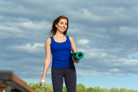 training session: young girl is preparing for a training session. standing with yoga mat and water bottle