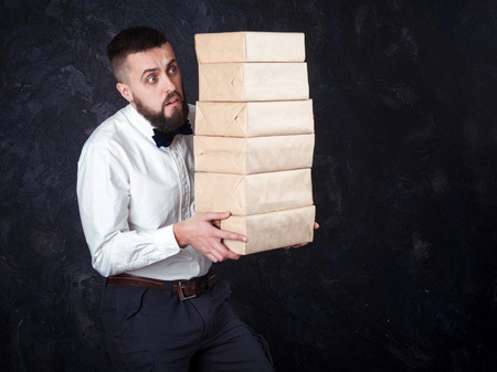 constraining: young bearded man carries a lot of boxes with gifts, fright