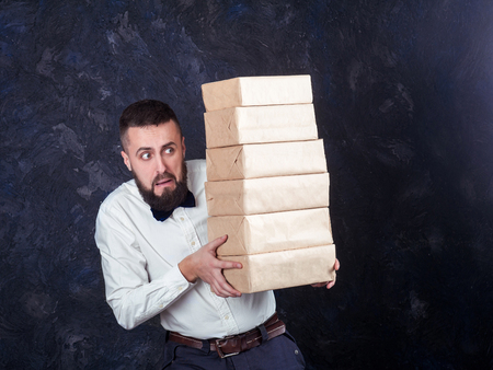 constraining: young bearded man carries a lot of boxes with gifts, surprise Stock Photo