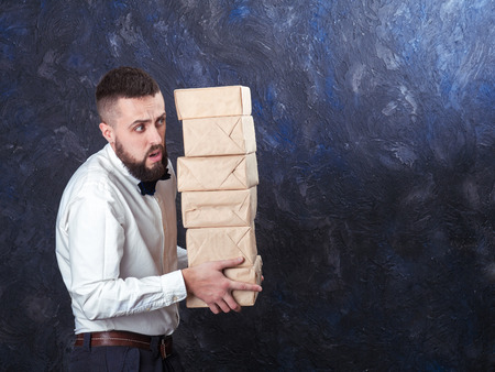 constraining: young bearded man carries a lot of boxes with gifts